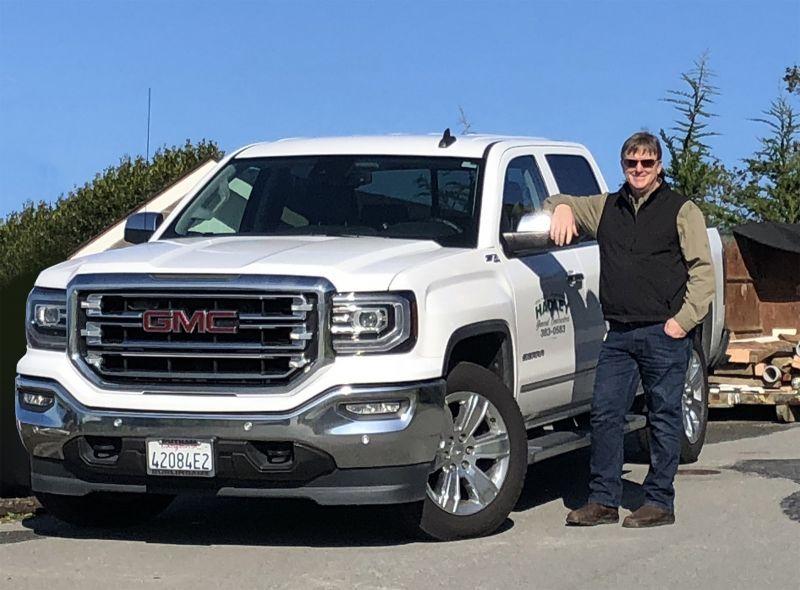 Hadley employee standing next to white truck.