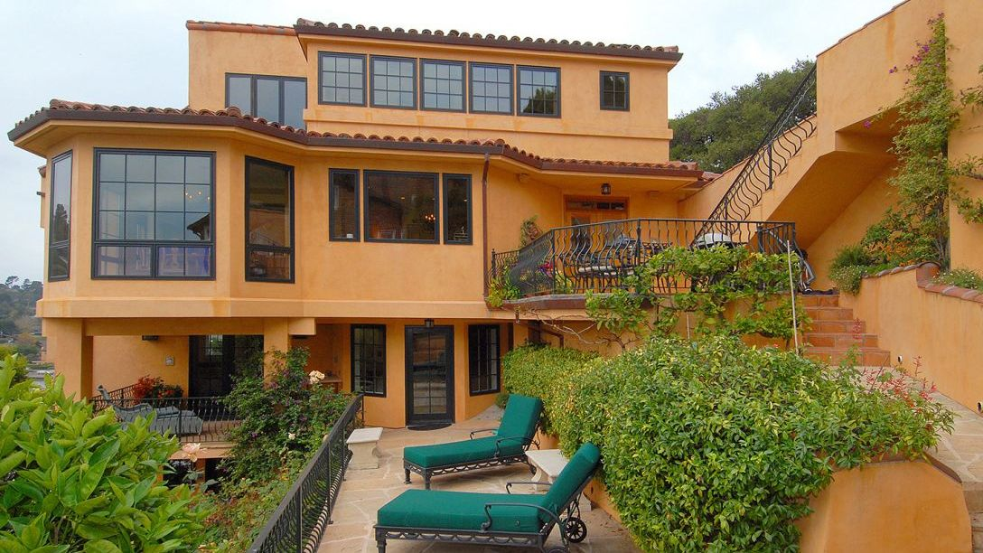 Spanish style 2 story home with lounge chairs and a balcony.