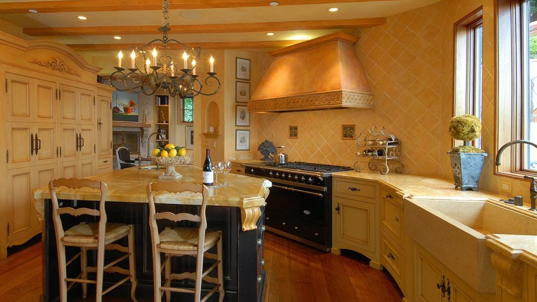 Full shot of kitchen with two barstools in front of the island counter and gas powered stove.