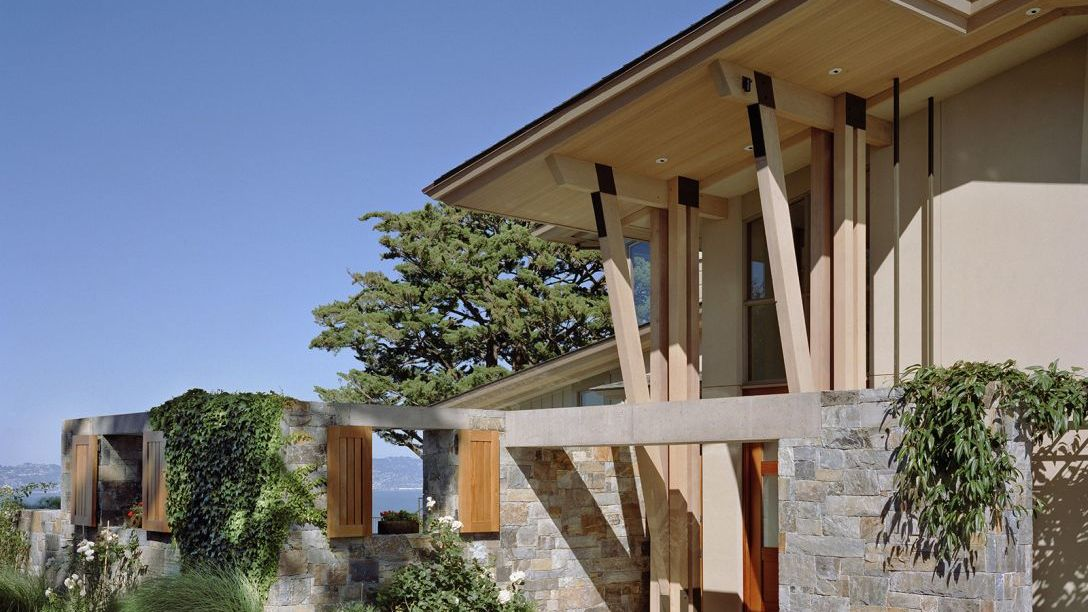 Front of modern home with wooden front door and wooden beams above.