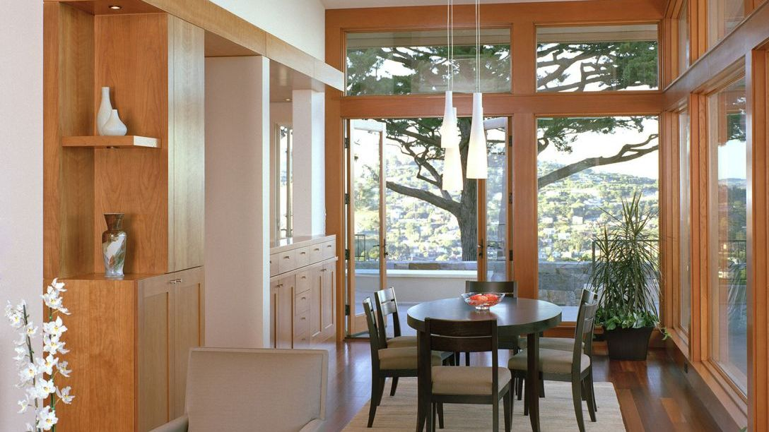Dark wood table in the dining area with wood floors and big windows overlooking the Belvedere area.