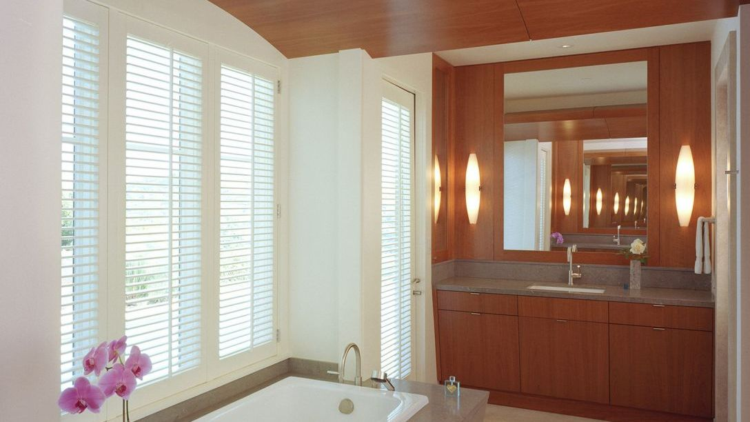 Bathroom featuring a white bathtub, windows and a wooden sink.