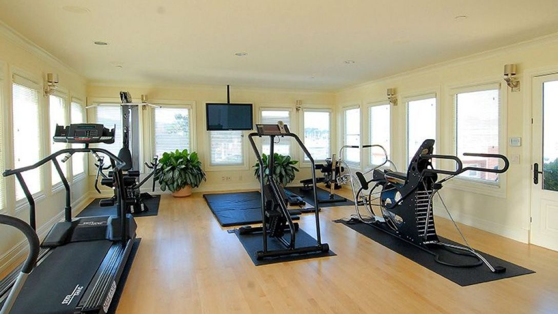 Exercise room with elliptical machine and treadmill.