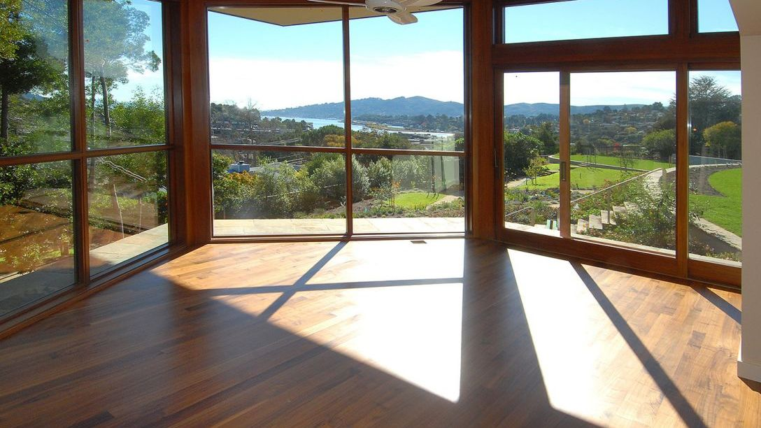 Room with wooden floors and large windows displaying views of four acre home.