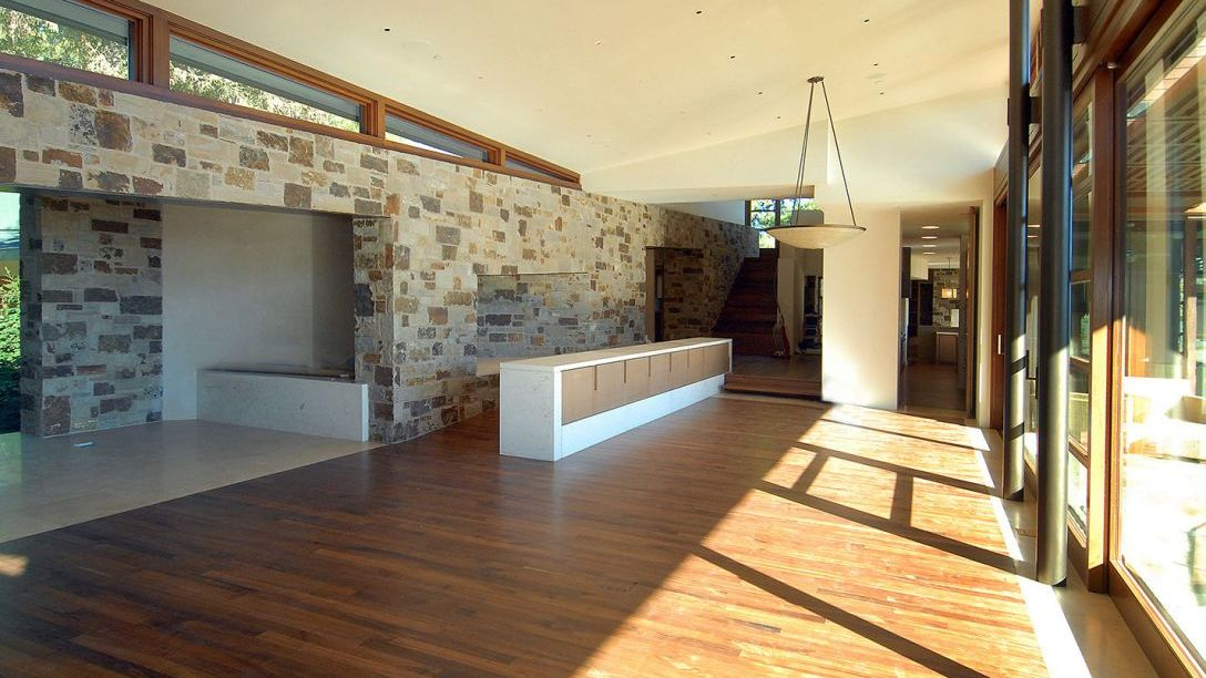 Wood flooring and cobblestone tiled walls.