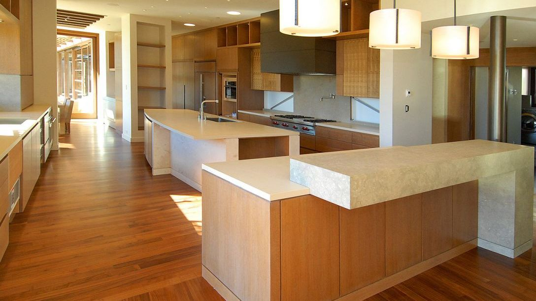 Wood paneled kitchen island with cream colored countertops.