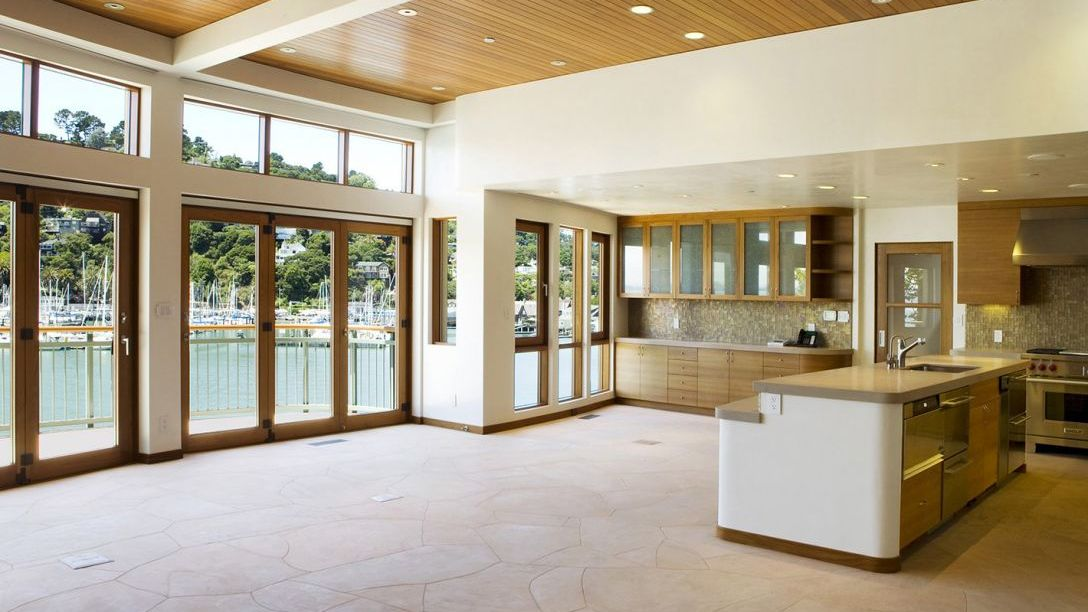 Spacious kitchen with wood paneled ceiling, kitchen island with gray countertops, and overlooking the Belvedere area.