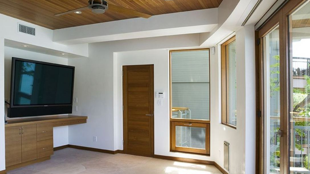 Television room with wood paneled ceilings.