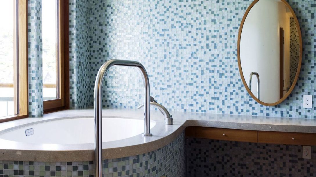 Blue, grey, and green mosaic tile bathroom with a white bathtub.
