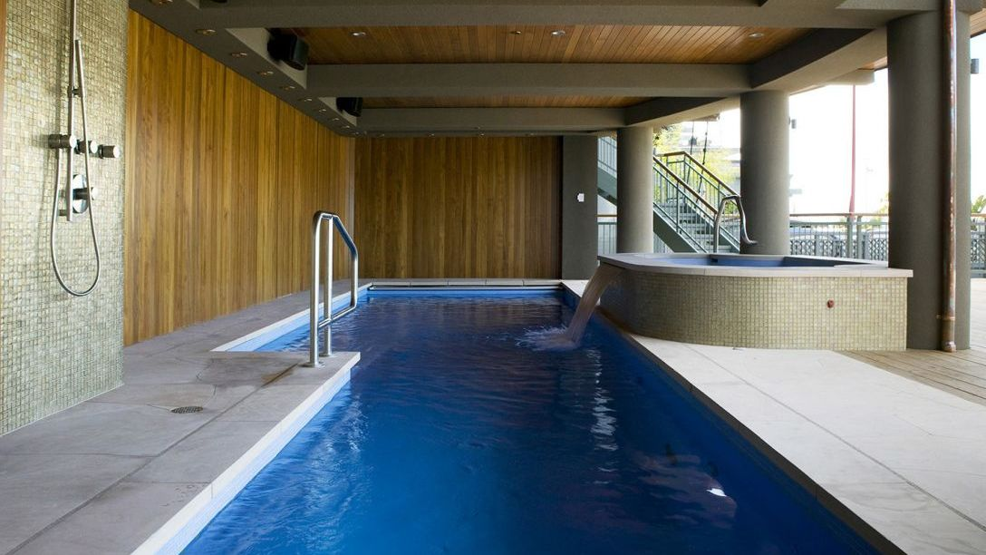 Swimming pool with a spa attached on the deck of home with wood paneled walls and ceilings.
