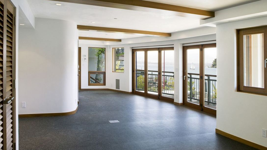 Open space room with white walls, wooden beams on the ceiling, and French doors opening up the view to the Belvedere area.