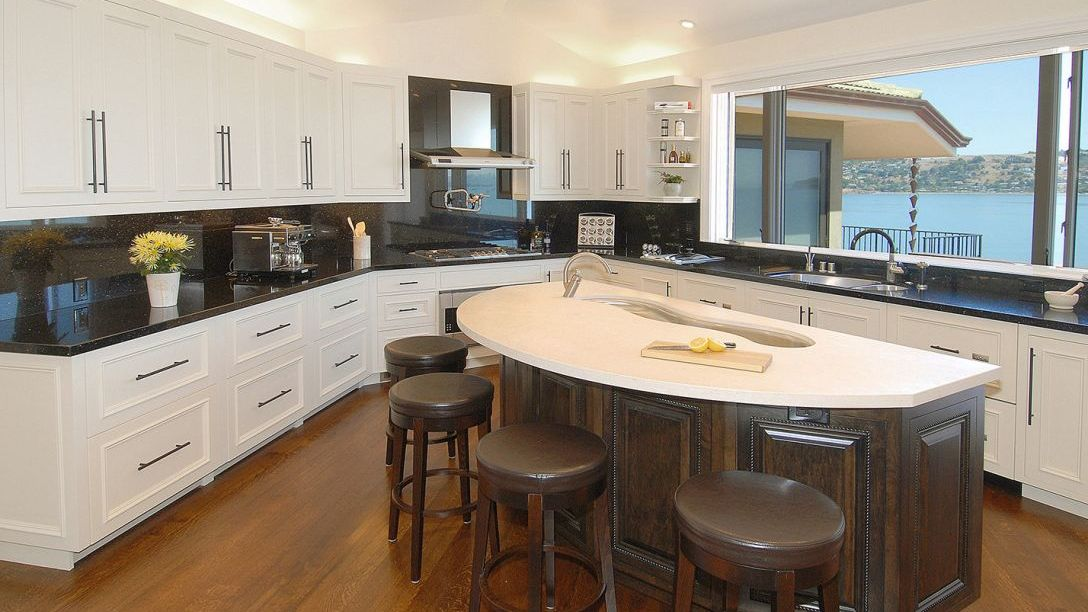Kitchen of Strawberry Peninsula remodel with hardwood floors, white countertop island, black marble countertops and white cabinets.