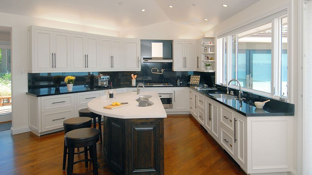 Kitchen of Strawberry Peninsula remodel with hardwood floors, black marble countertops and white cabinets.