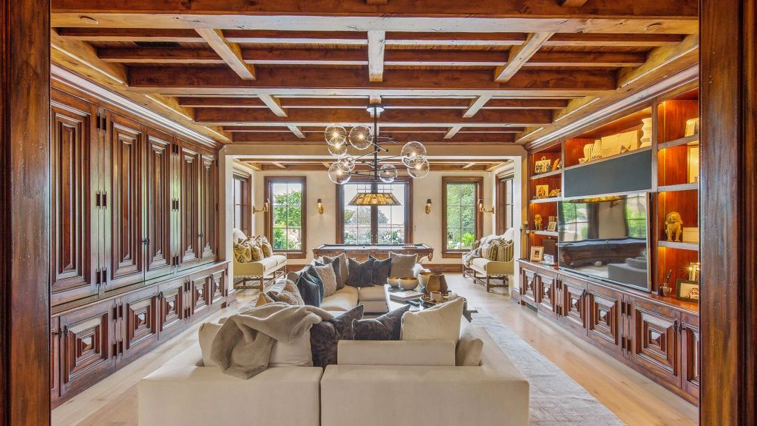 Family room with beige couch and wooden beam ceiling
