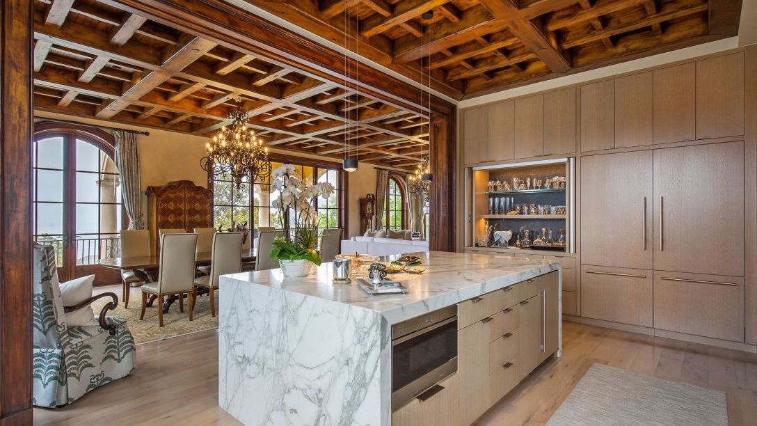 White marble countertop in kitchen with wood beam ceiling.