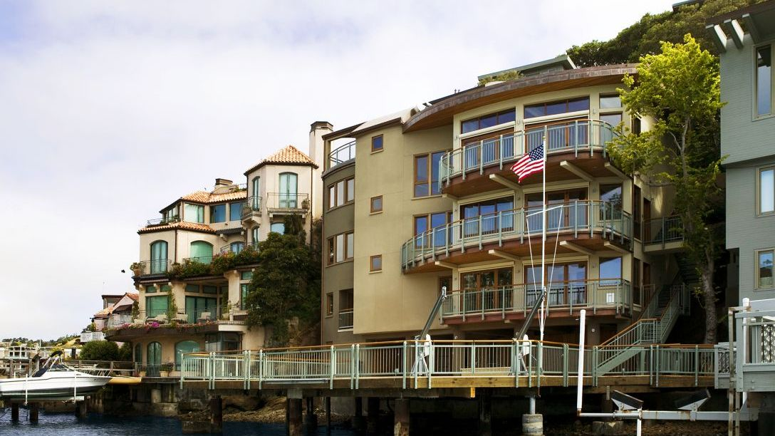 Exterior of tan multi-story home with turquoise and wood railing.