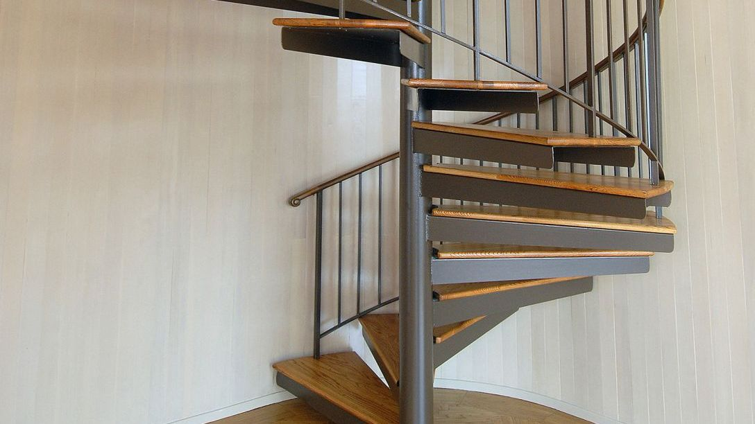Spiral staircase with wood steps and metal railing.