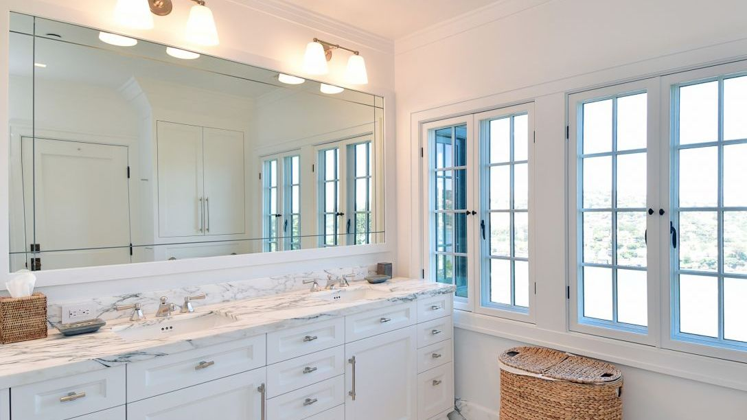 Bathroom with twin sinks, white cabinets and countertops.