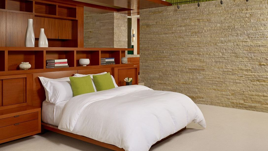 Bed with green throw pillows in Mill Valley remodel home.