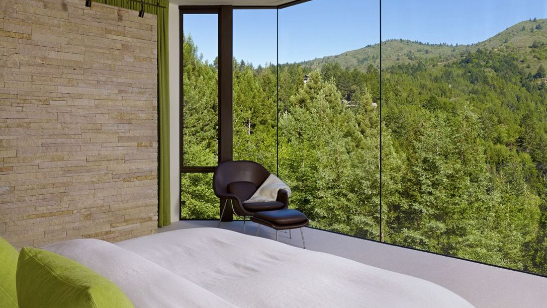 Bed with green throw pillows facing glass window with view of trees.
