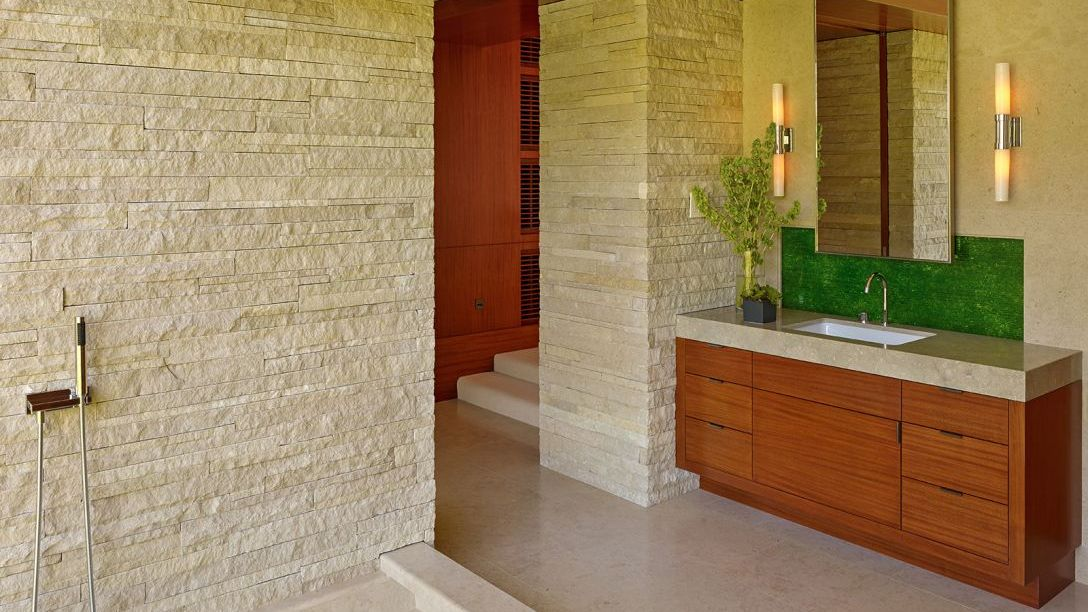 Bathroom with beige slate walls and wooden cabinets.