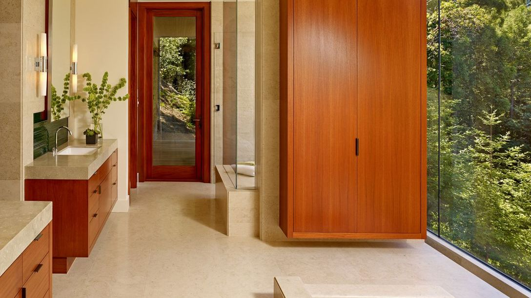 Mill Valley remodeled bathroom with beige marble and wood cabinets.