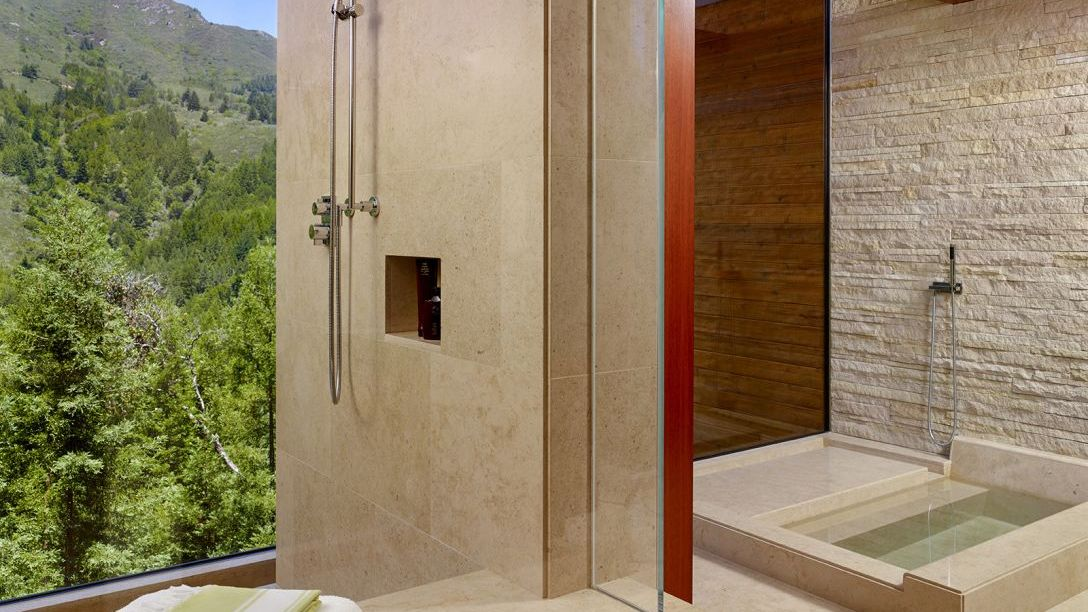 Beige marble bathroom with walk-in shower and separate bathtub.