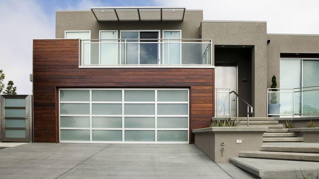 Closer shot of cement driveway and glass garage doors.