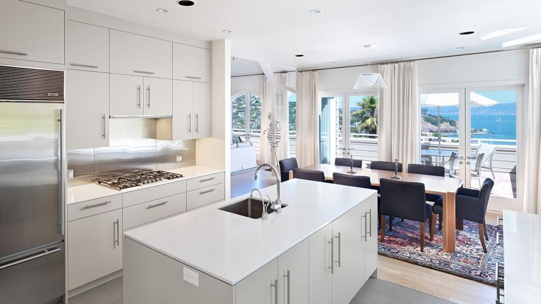 Belvedere Modern remodel kitchen with stainless steel fridge, white cabinets and countertops.