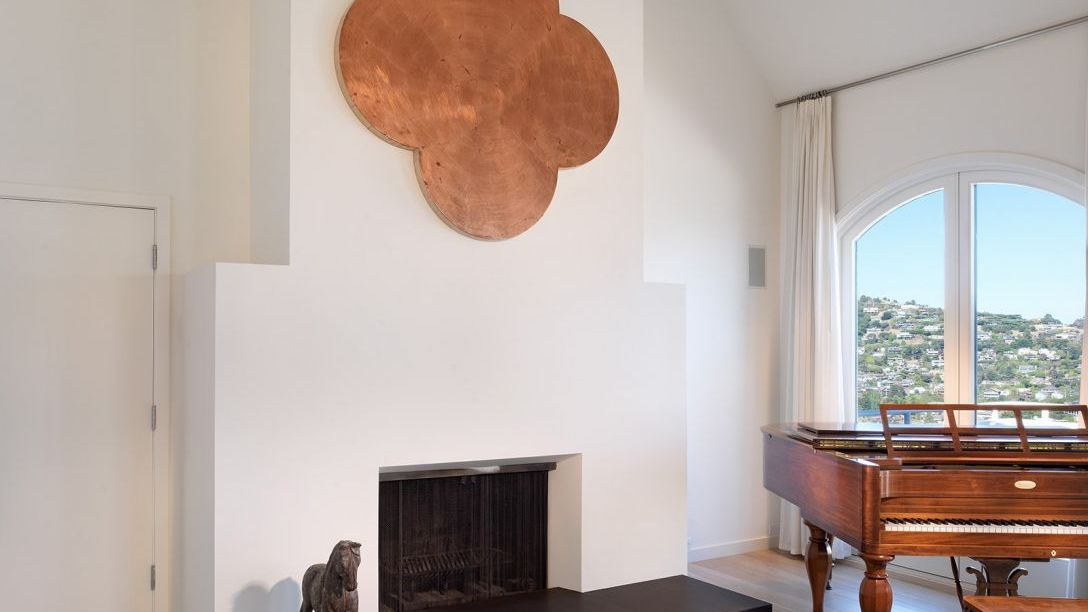 White fireplace and brown piano in Belvedere Modern remodel.
