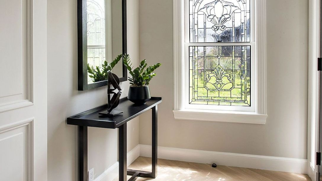 Black table in front of mirror mounted on wall.