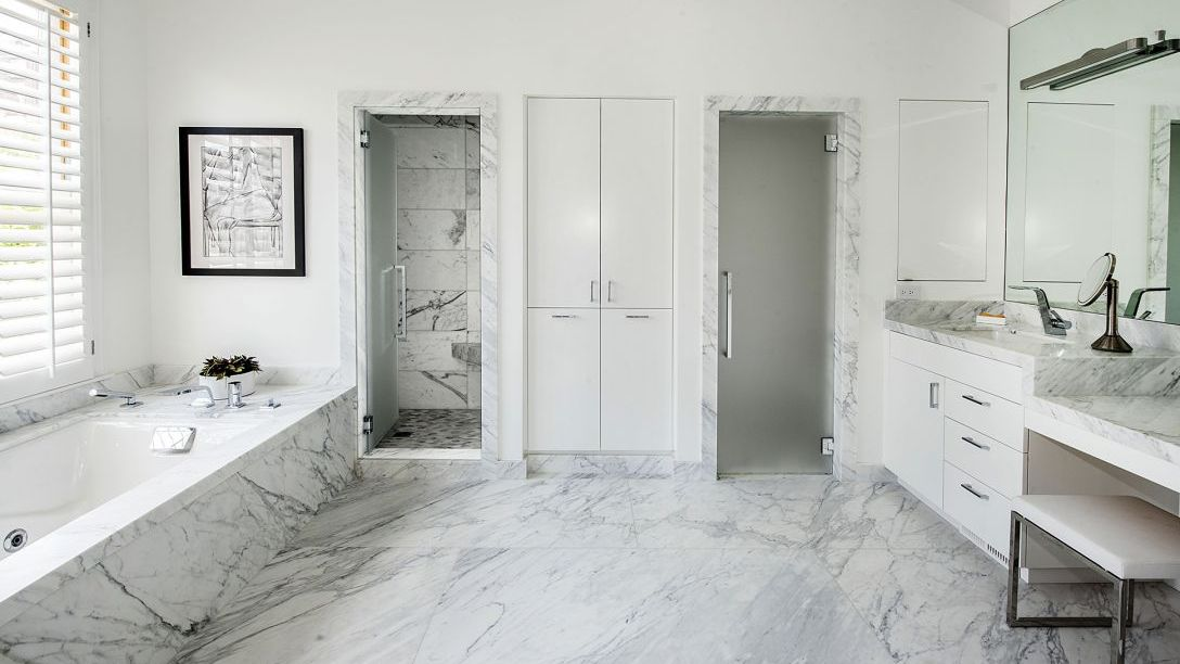 Master bathroom of Pacific Heights remodel with white marble bathtub, floor, and showers.