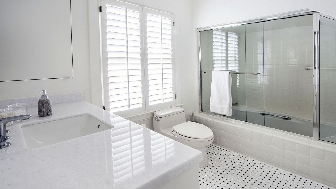 Bathroom with white toilet, black and white specked tile, shower with sliding glass doors, and white marble sink.
