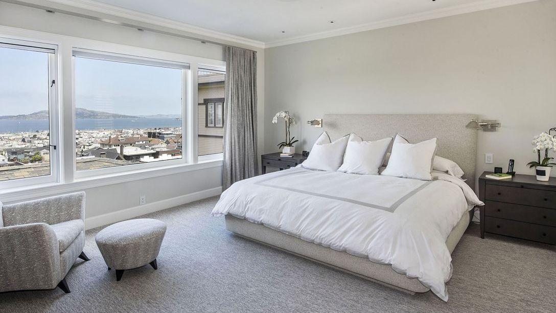 White bed in master bedroom of remodel.