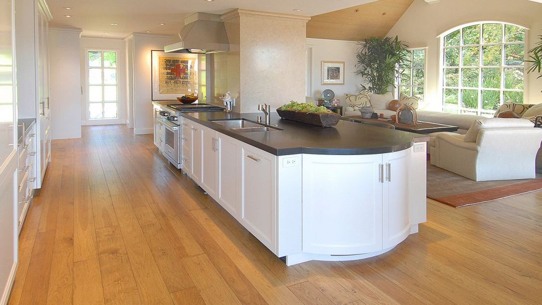Kitchen of Tiburon Hillside remodel with black countertops, white cabinets, and wood floors.