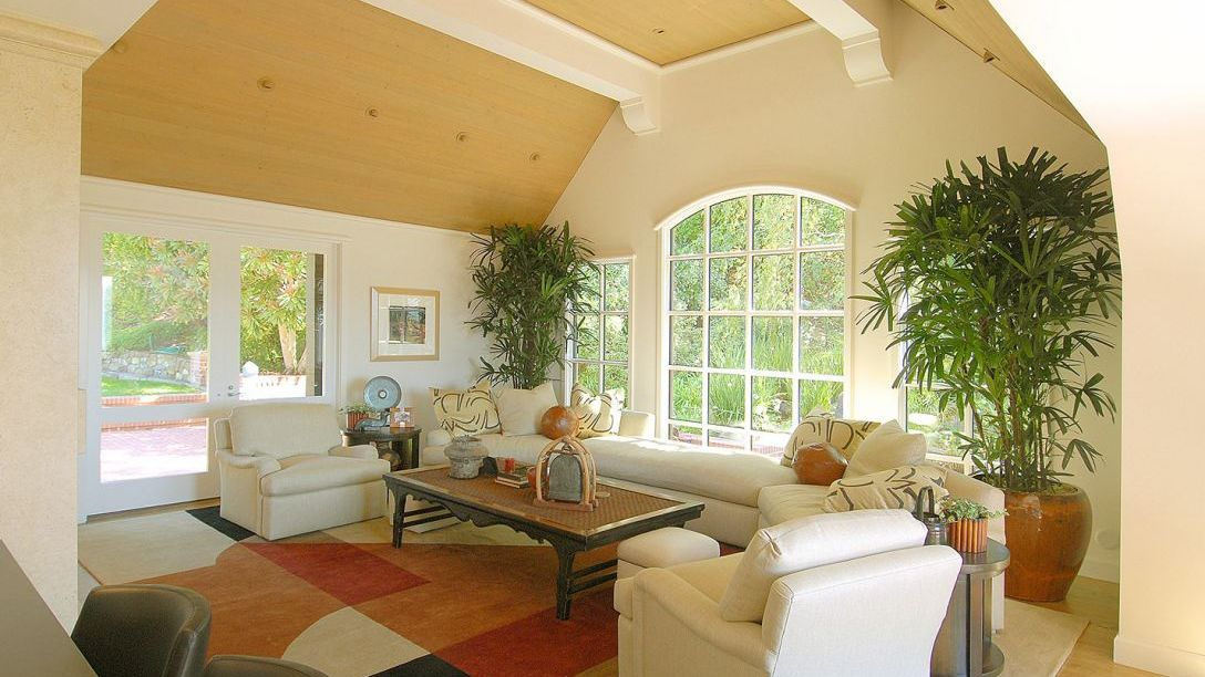 Living room of Tiburon Hillside remodel with white puffy chair, multicolored rug, and wood ceilings and floor.