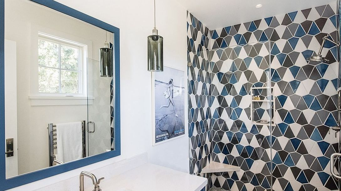Blue tiled bathroom with walk in shower.
