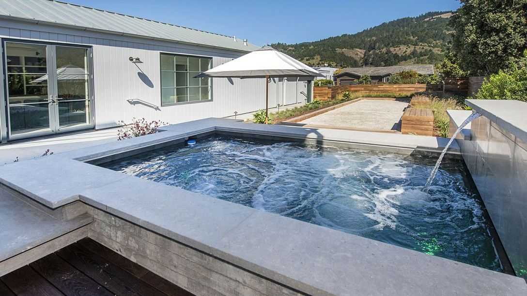 Outdoor jacuzzi attached to a garden and bocce ball court.