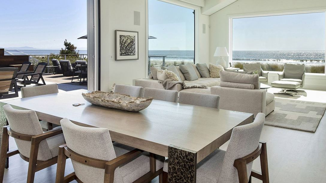 Wood dining table with cream colored chairs and a view overlooking the deck to the beach.