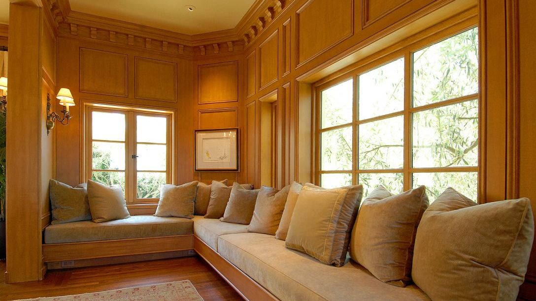 Trapezoid window seating with wood walls.