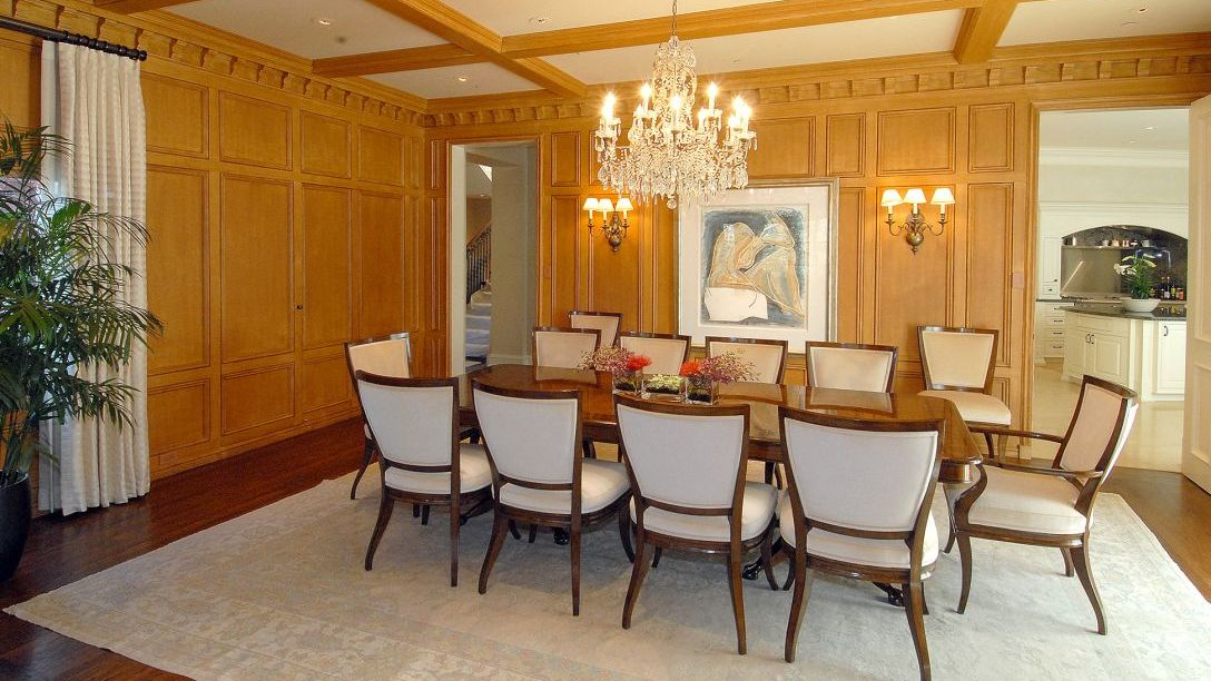 Dining table in dining room with wood paneled walls.