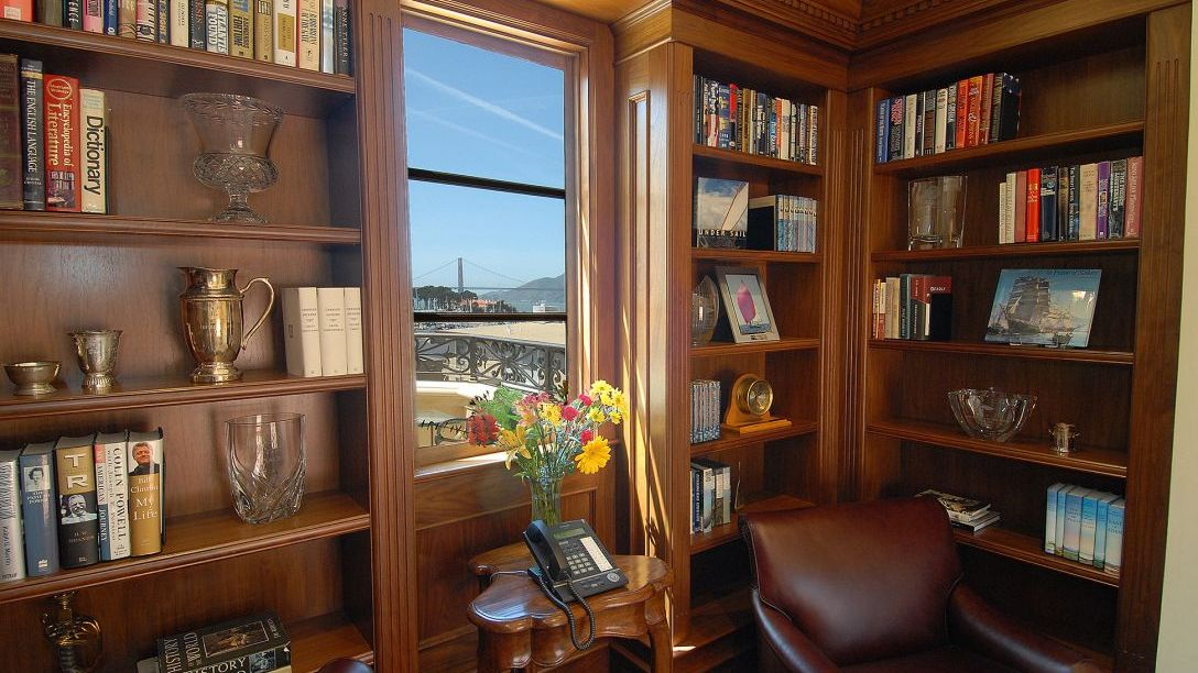 Wood bookcase in study with window viewing the Golden Gate Bridge.