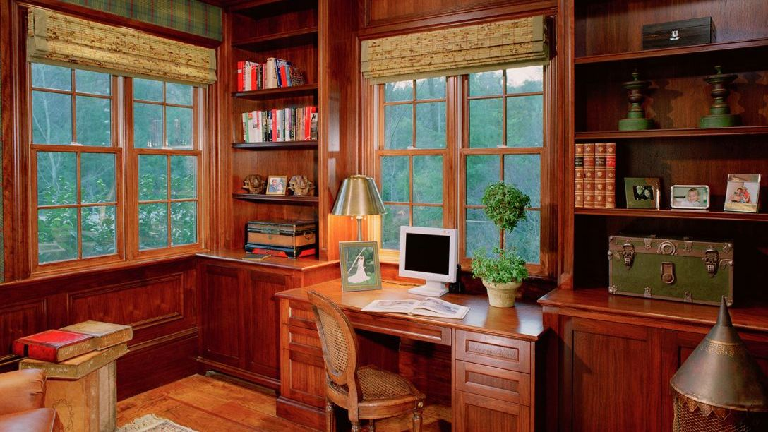 Wooden desk in Ross Remodel  study with wood floors and wall mounted wooden bookcase.
