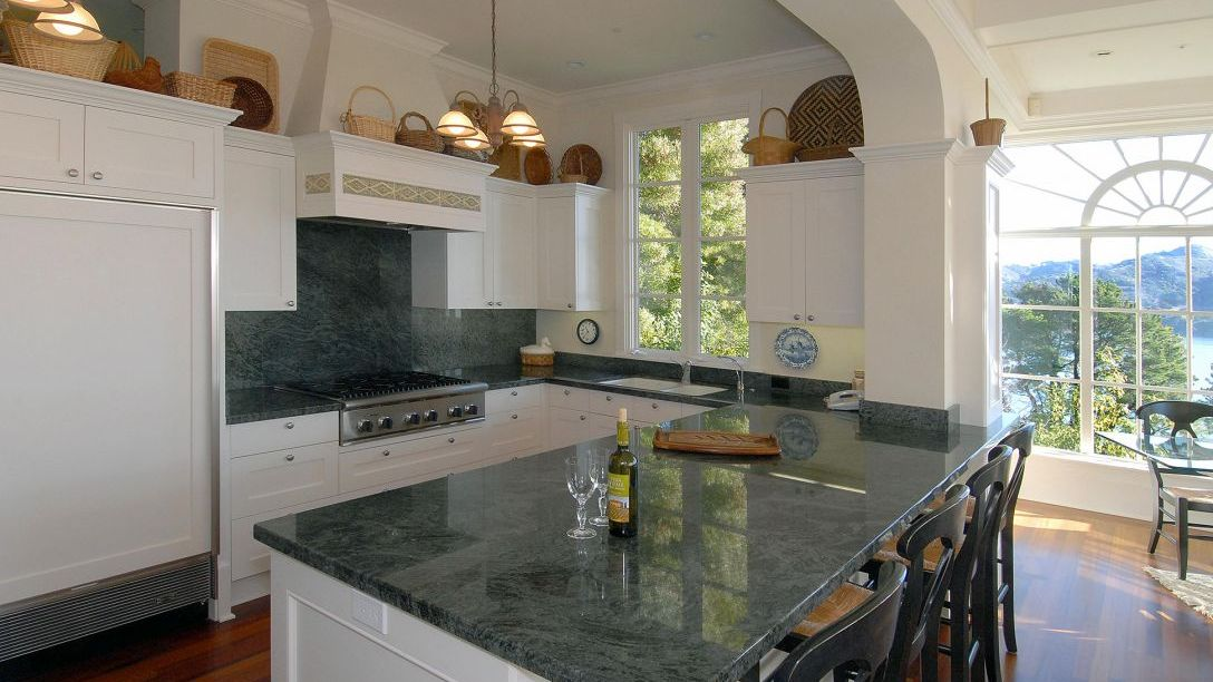 Black marble kitchen countertops with white cabinets.