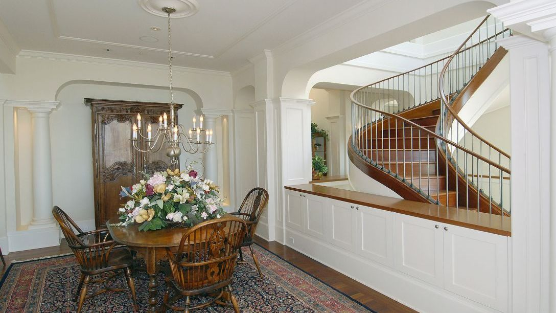 Wood dining room table with multicolored rug and spiral staircase in background.