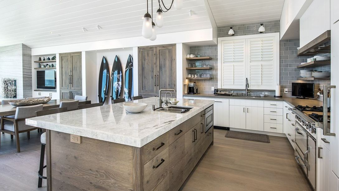 Wooden island with white marble countertops in kitchen.