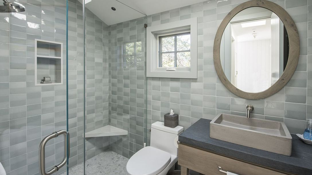 Grey tiled bathroom with white toilet and walk in shower.