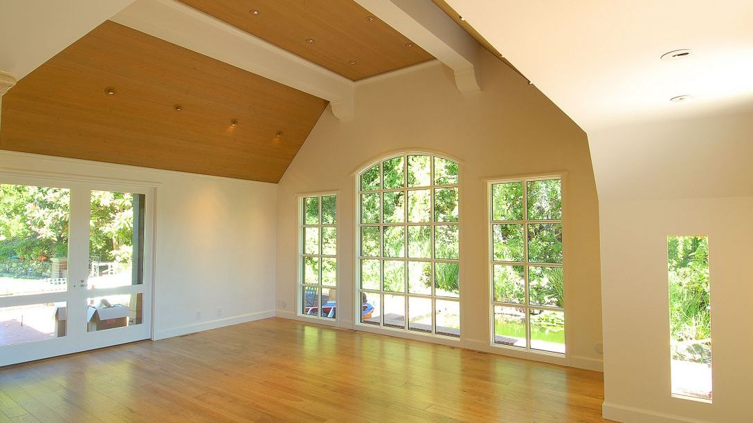 Empty room with wood floors and wood paneling on the ceiling of Tiburon Hillside remodel.