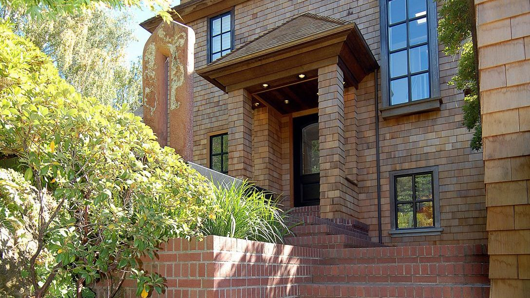 Porch of Tiburon Hillside remodel with brick stairs and black front door.