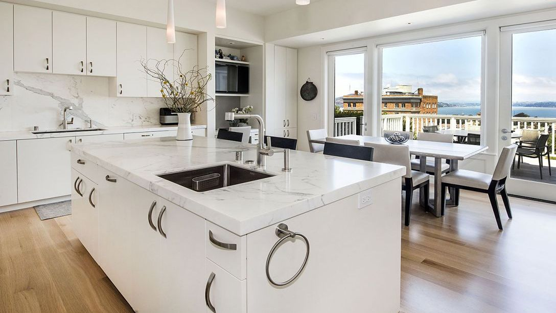 Pacific Heights remodel kitchen with white marble countertops, wooden floor, and windows overlooking the view of the Bay.